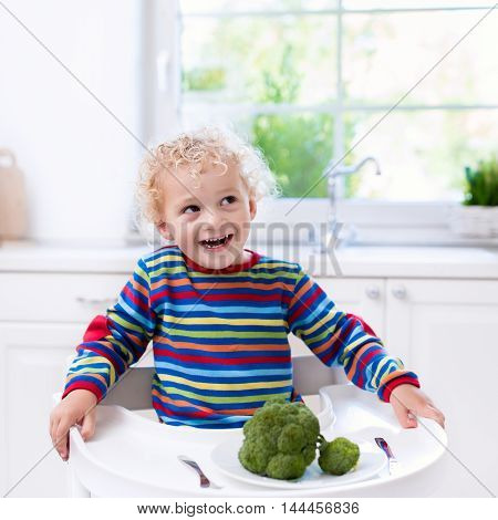 Happy baby sitting in high chair eating broccoli in a white kitchen. Healthy nutrition for kids. Bio vegetable as solid food for infant. Children eat vegetables. Little boy having lunch at home.