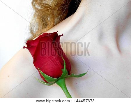 Small red rose on the shoulder of a red-haired skinny girl