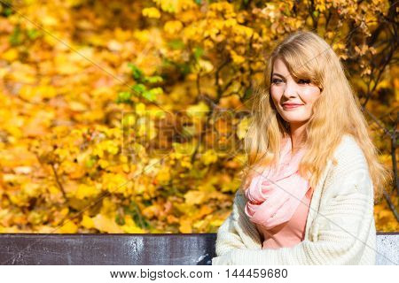 Season happiness and people concept. Young fashionable blonde woman sitting on bench in autumnal park on sunny day