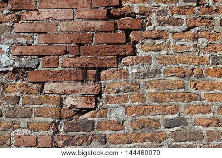 Texture of the red brick wall with big crack