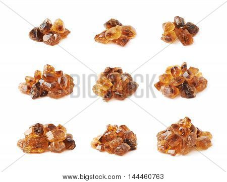 Pile of brown rock sugar crystals isolated over the white background, set of nine different foreshortenings