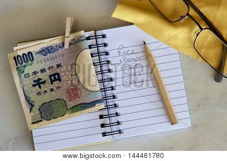 Shopping list in a notebook with Japanese currency and spectacles.