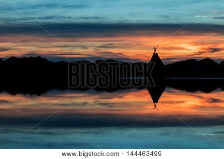 Tepee on a lake shore with the water giving a wonderful reflection of the sunset.