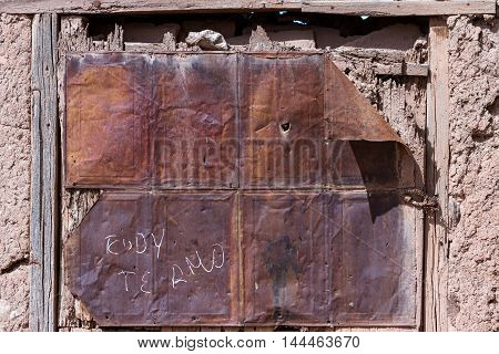 close up of an old abandoned house focused on a window covered with a rusted piece of sheet metal