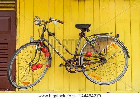 retro bicycle hang on yellow wood wall