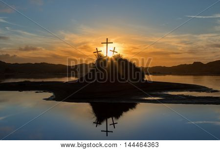 Three crosses on a Island with the sun setting behind it.