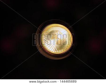 Clear white light bulb against dark background