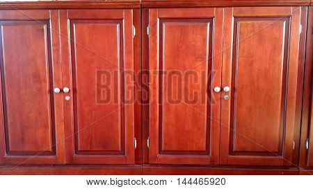 reddish varnished locking wooden storage cabinets with white knobs, recessed panels, Ranot, Thailand