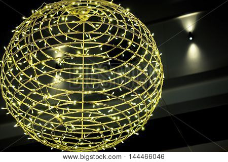 Decorative skeletal ball wound with lots of yellow Christmas lights, giving multitude point-source illumination.