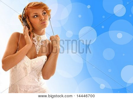 Sexy redhead listening to the music over abstract background