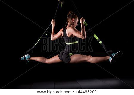 One young attractive woman does splits crossfit stretching with trx fitness straps in the gym's studio on black background