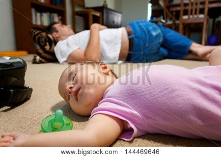 A newborn baby and her father lay sleeping on a family room floor. The exhaustion of having a new baby has set in.