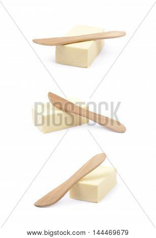 Wooden knife over a briquette piece of a butter, composition isolated over the white background, set of three different foreshortenings