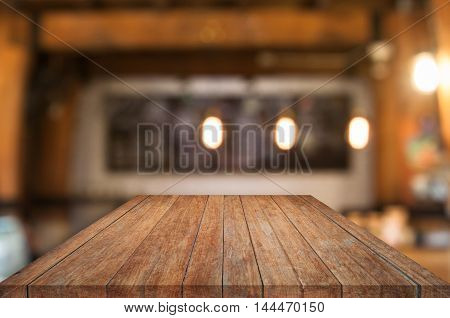 Perspective wooden table top with coffee shop blurred abstract background