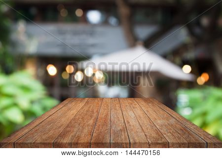 Perspective wooden table top with cafe blurred abstract background