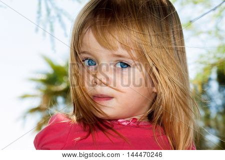 A little blue-eyed girl stands with peeking through strands of her own hair as they blow in the breeze.