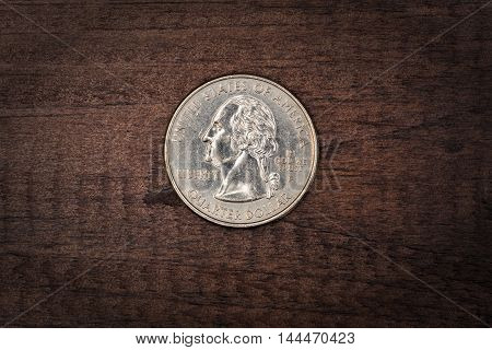 Twenty Five cents of dollar coin on wooden background
