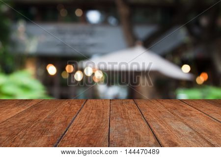 Wooden table top with cafe blurred abstract background
