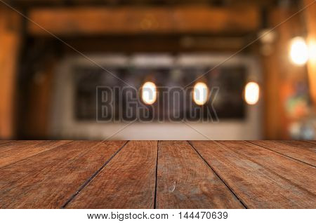 Wooden table top with coffee shop blurred abstract background