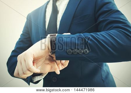 Fashionable Businessman In Elegant Blue Suit Looking At Luxury Watch In Hurry
