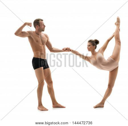 Acrobatics. Strong man posing in pair with graceful girl