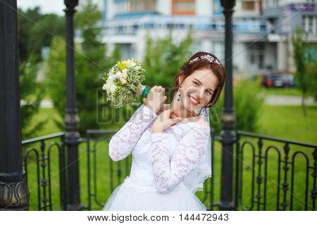 Young happy bride on her wedding, photosession in park