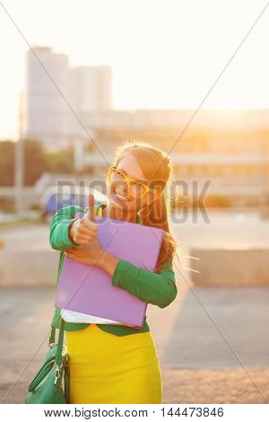 Business woman holding a folder. Girl in glasses and jacket friendly smiles and shows thumb up. Young and successful.