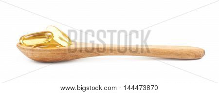 Wooden serving spoon full of softgel pills isolated over the white background