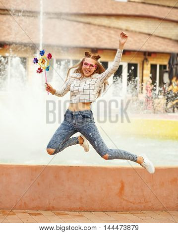 Lovely cheerful girl teenager jumping with a Spinner toy. Summer holidays.