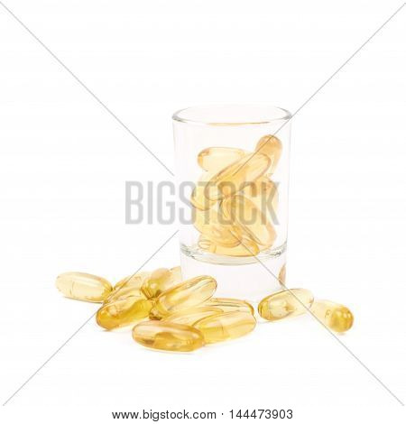 Shot glass full of softgel pills isolated over the white background