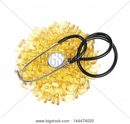 Pile of yellow softgel medical pills with a stethoscope over it, composition isolated over the white background