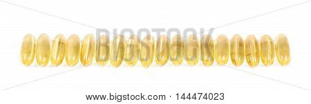 Line of yellow softgel pills isolated over the white background