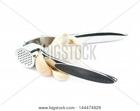 Metal garlic press utensil next to a pile of fresh cloves isolated over the white background