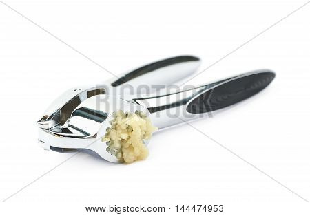Used metal garlic press utensil with a crushed clove, composition isolated over the white background