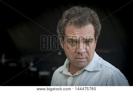Portrait of a sad man in a light jacket on a black background