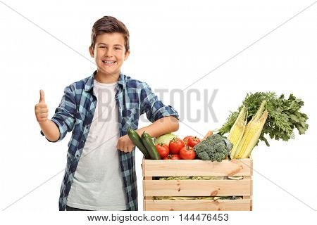 Happy kid posing next to a crate full of groceries and giving a thumb up isolated on white background
