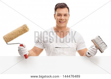 Young painter posing behind a blank panel isolated on white background