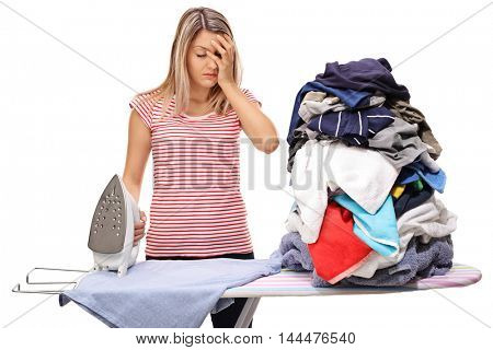 Sad woman posing next to a big pile of clothes and an ironing board isolated on white background
