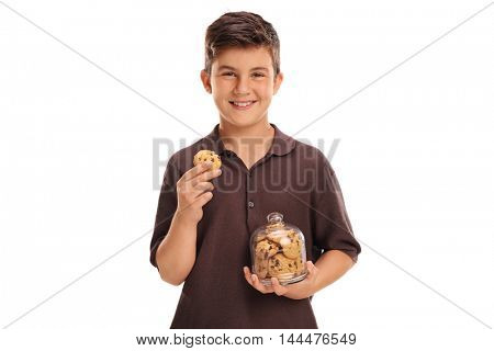 Cheerful child holding a cookie and a jar of cookies isolated on white background