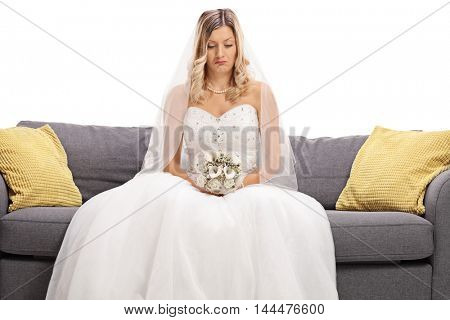 Depressed bride seated on a sofa isolated on white background