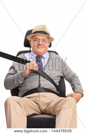Senior man sitting on a car seat and fastening his seatbelt isolated on white background