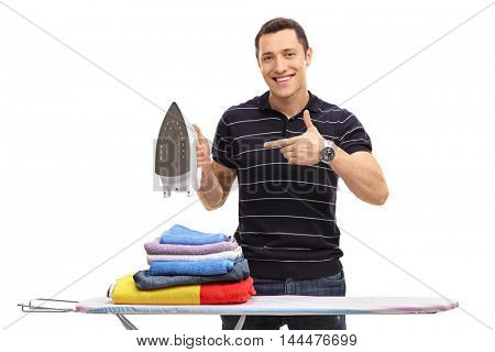 Cheerful man holding an iron and pointing at it isolated on white background