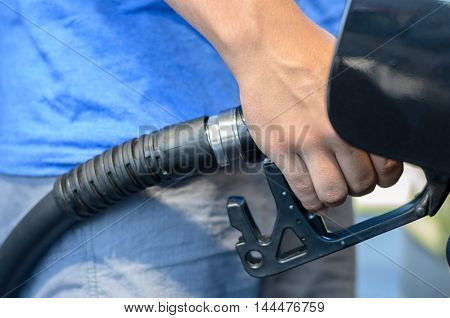 Man filling his car with gasoline at a garage or filling station close up view on his hand and the nozzle as he dispenses the fuel