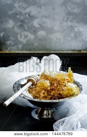 honeycomb in a vintage bowl with white fabric on grey background