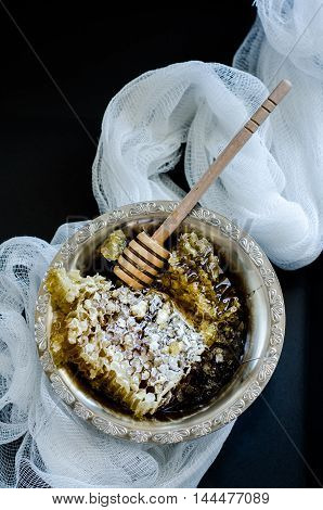 Top wiev of honeycomb in a vintage bowl with white fabric on black background