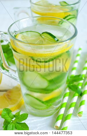 cold summer drink with lemon mint and cucumber on a white background