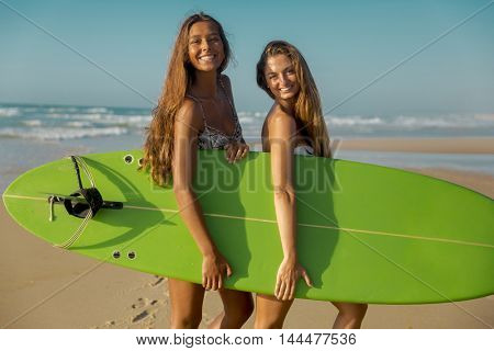 Best friends enjoying the summer, posing with a surfboard on the beach