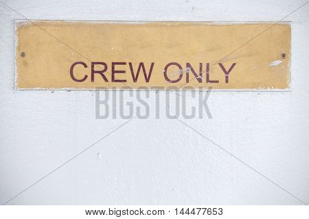 Color image of a placard wit 'Crew Only' written on it.