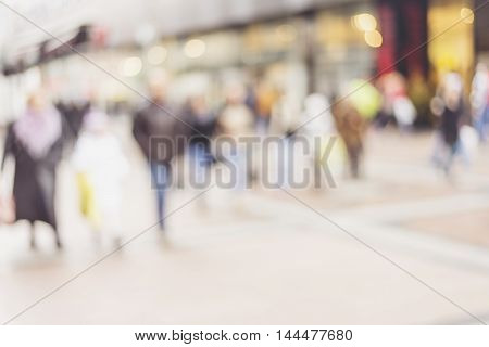 People rush on the street. Blurred crowd of different people are walking in the city. Defocused background of city life. Evening with lights.