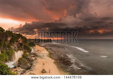 Colorful sunset on Balangan Beach in Bali, cliff view.